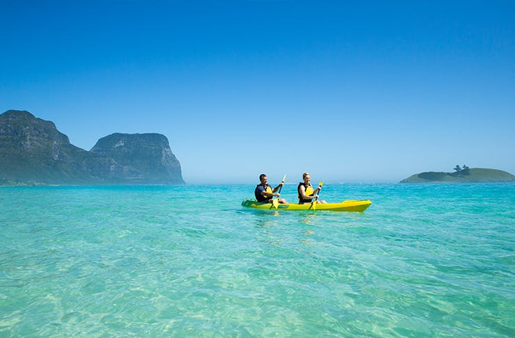 two people kayaking on clear waters with mountain behind