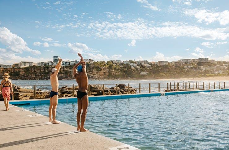 two people standing at edge of ocean pool