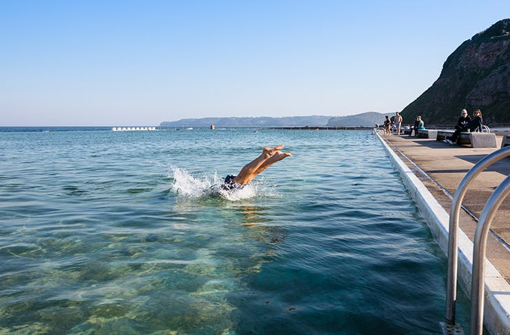 person diving into coastal pool on clear day