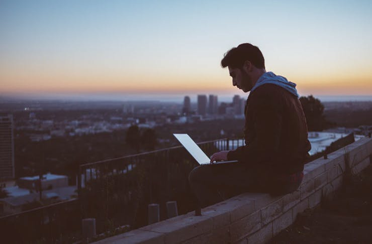 man sitting on top of roof with skyline of city holding laptop