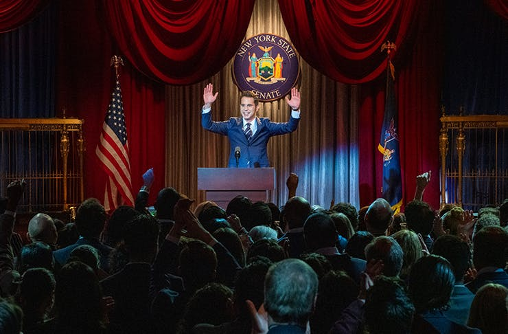 man standing at podium addressing room of people