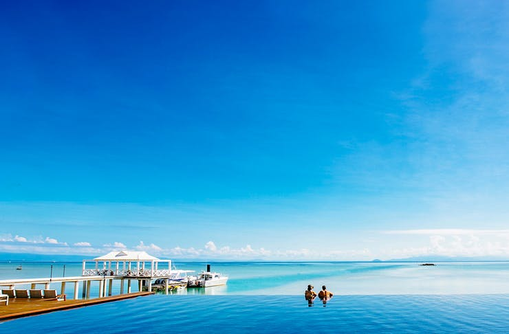 two people in stunning infinity pool on the ocean