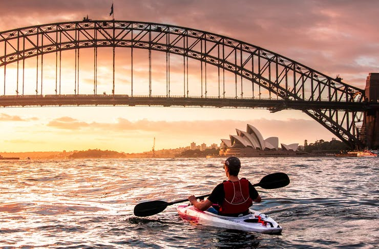 person kayaking at sunrise in sydney harbour before the harbour bridge