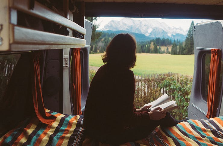 girl sitting inside travel van with book and van back doors open overlooking mountainous landscape