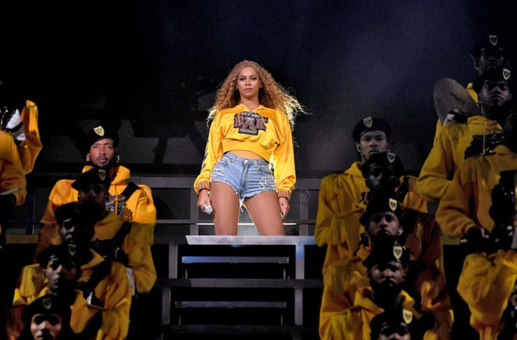 beyonce stands in the middle of the stage at coachella with her troop of dancers.