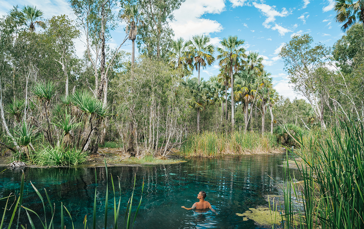 A man swims in the crystal clear waters of Bitter Springs