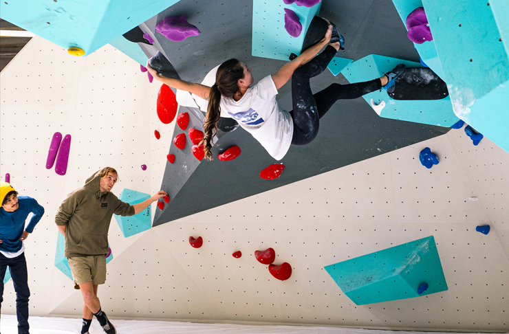 girl climbing bouldering wall with two friends cheering on the groudn