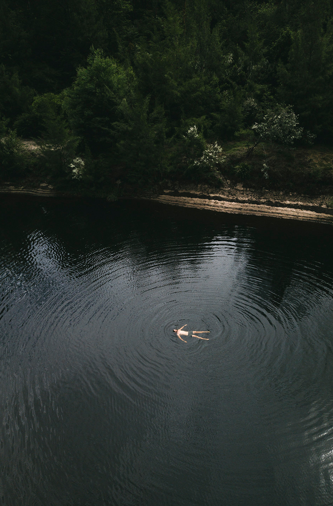 man floating on back in bush swimming hole