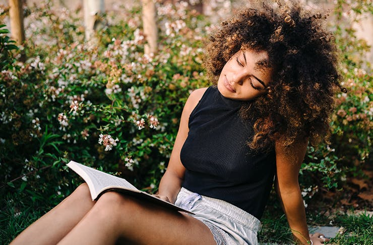 young mixed race woman reading book in corner of a leafy garden.