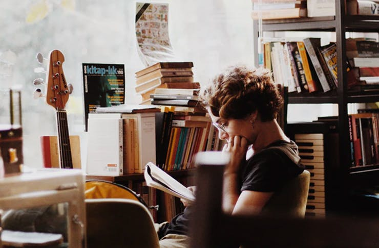 person sitting in bookshop reading by the window
