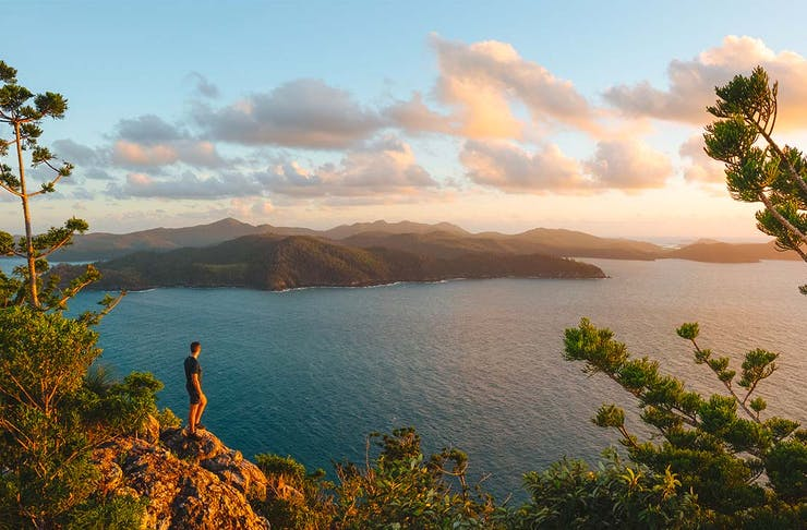 a man stands on a cliff looking out a cluster of stunning islands