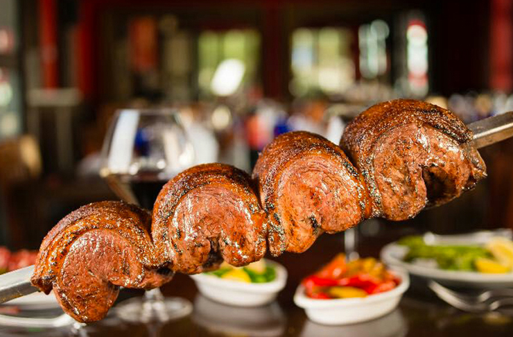 Carne cozida lentamente em haste de metal