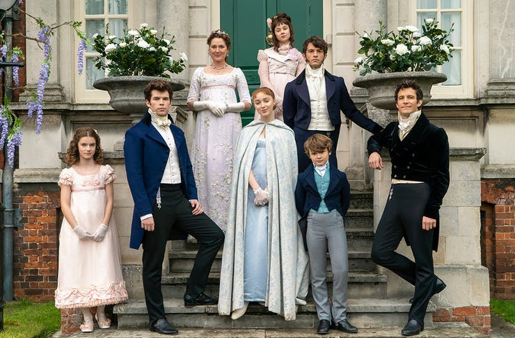 The cast of the Bridgerton family pose on steps outside a stately house