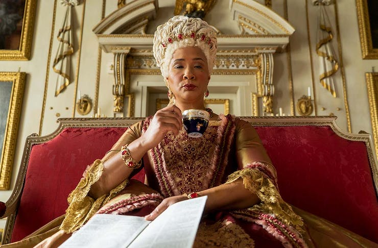 Queen Charlotte of Bridgerton holds a paper and sips a cup of tea.