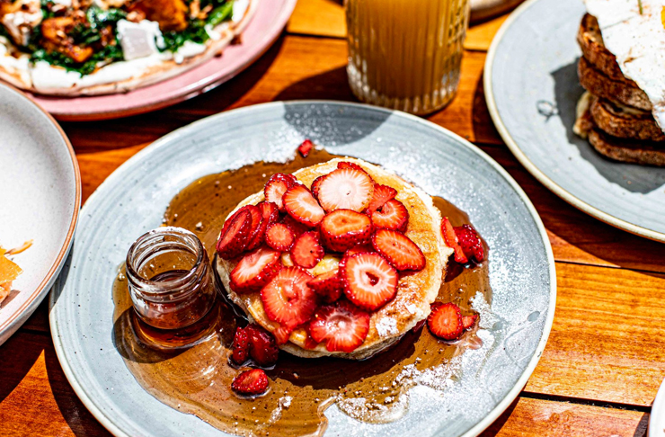 strawberry pancakes on plate with syrup