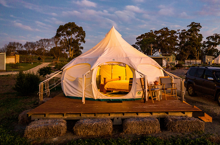 glamping style tent on deck with hay on a farm