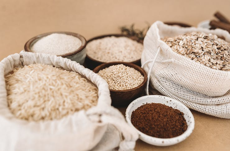 Hessian bags are filled with rice and rolled oats. Around it are small ceramic bowls filled with sugar and powder.