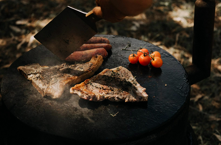 beef and tomatoes on hot plate in the bush