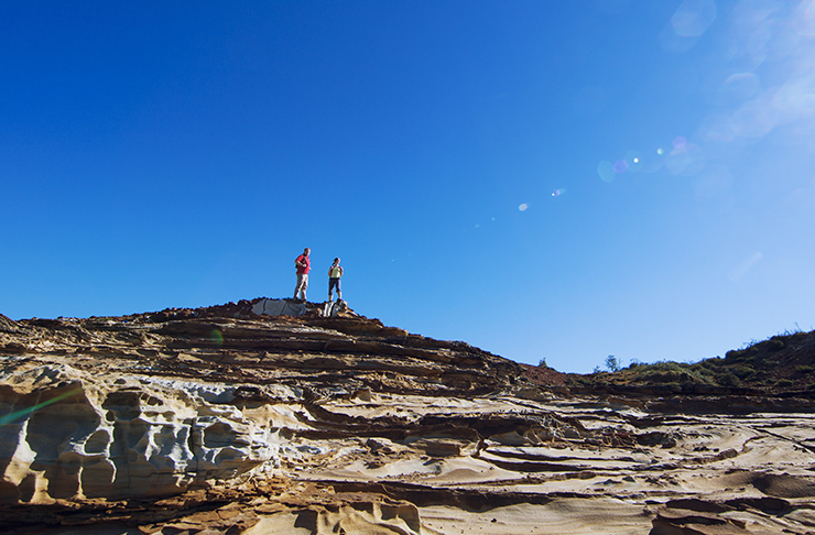 two people standing on top of white coastal cliffs