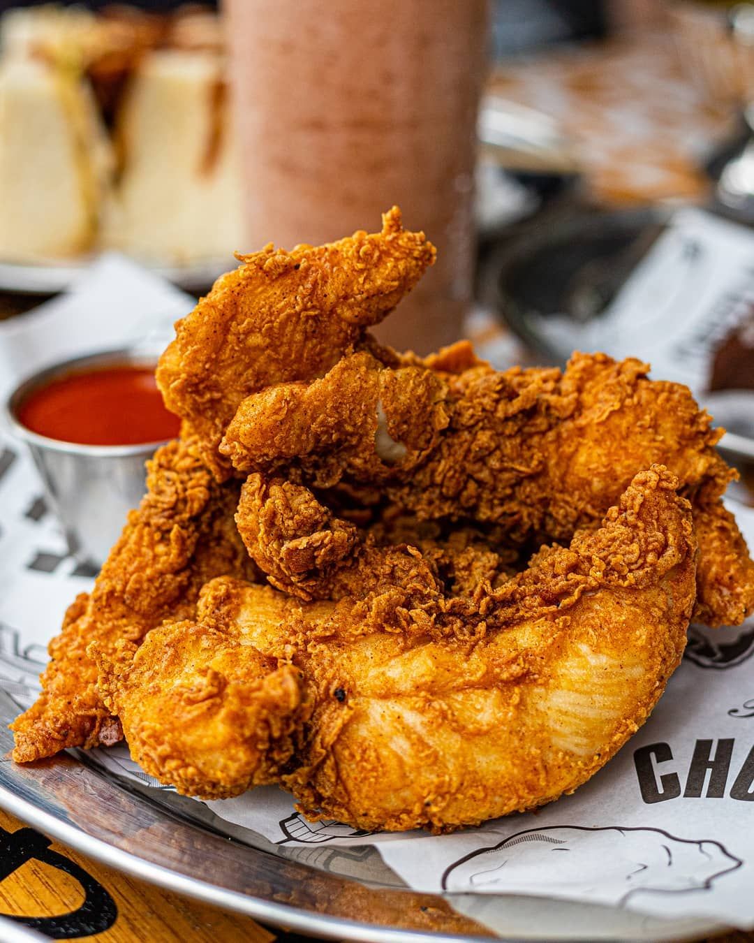 Crispy fried chicken on a silver platter with a tub of red sauce in the background.