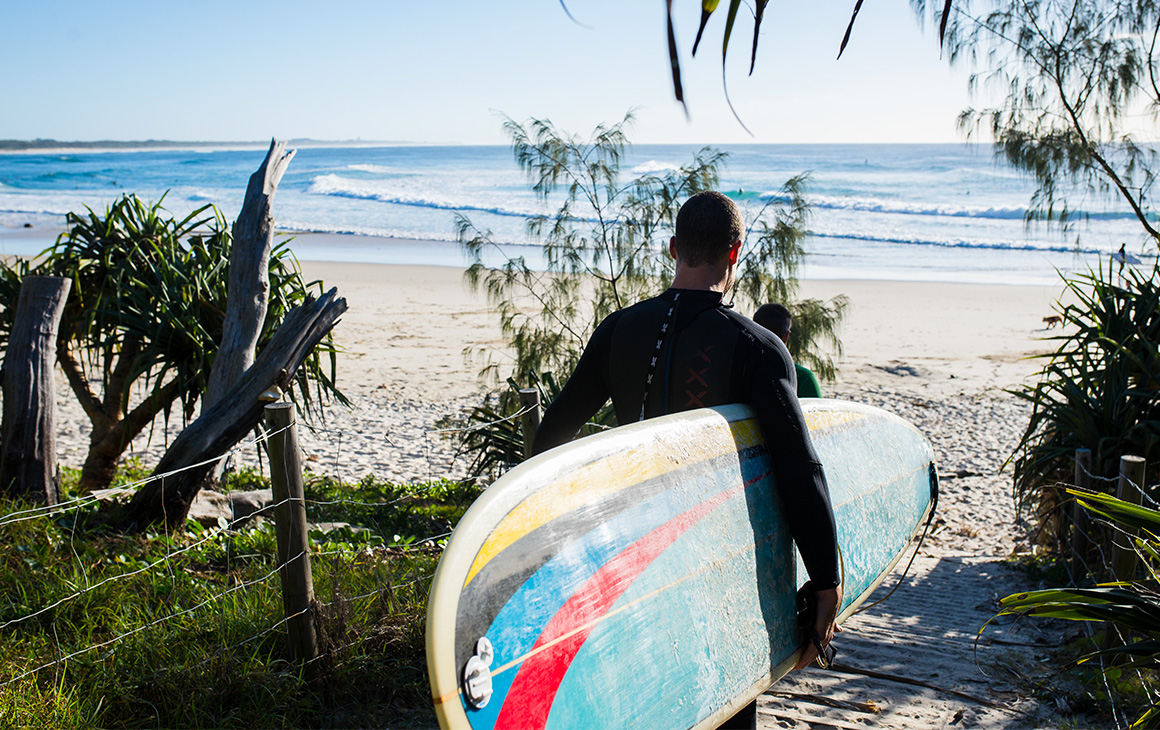 a man holding a surf board walks into the ocean