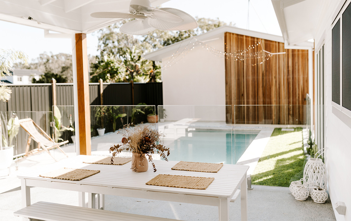 a pool is covered by a canopy of fairy lights. In front is an outdoor dining area with table and chairs.