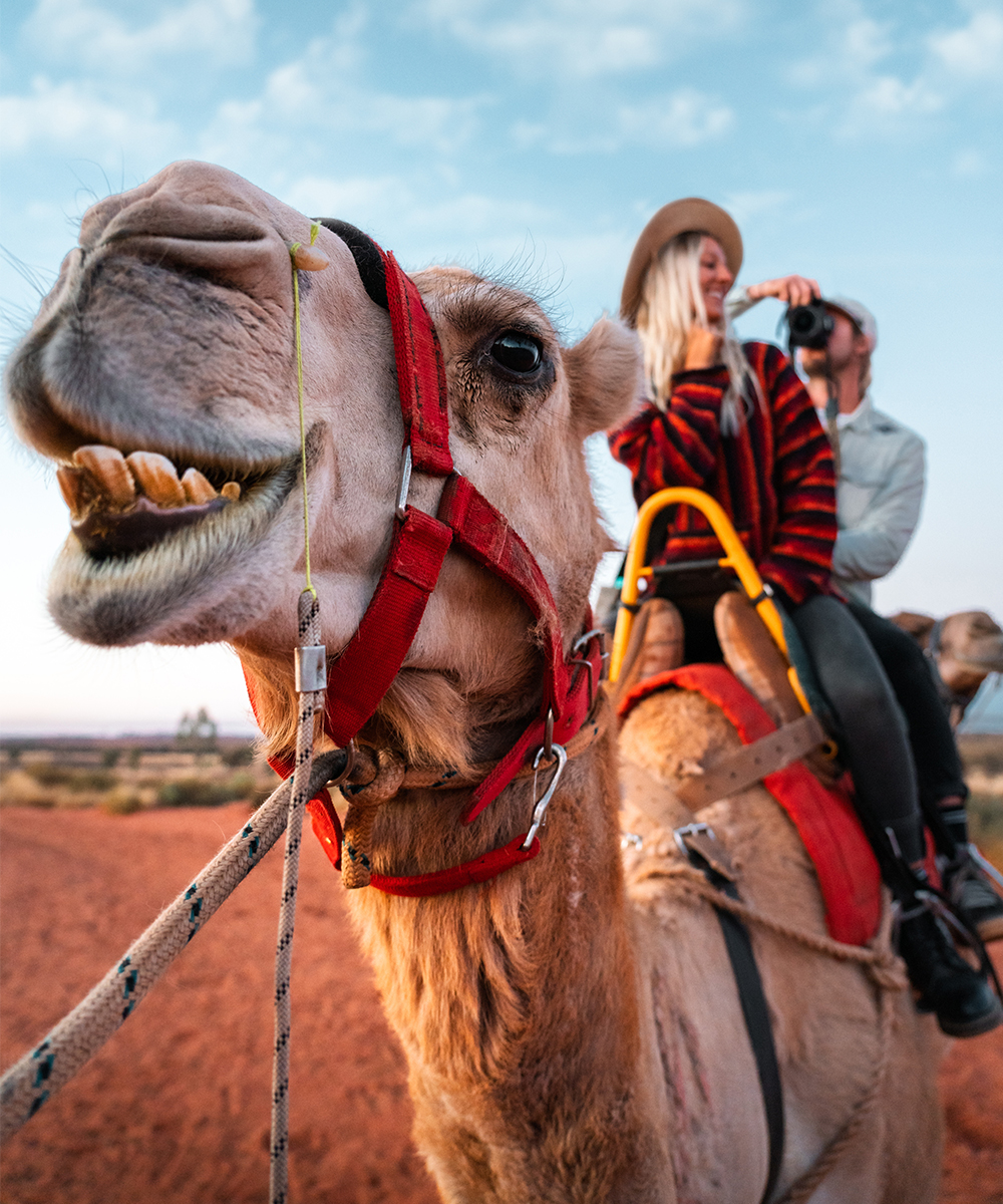 a man and woman ride a camel in the desert.