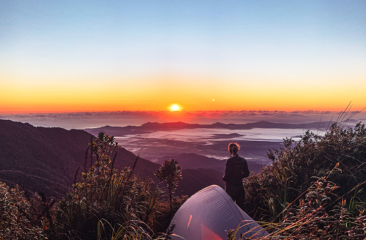 person camping on top of mountain at sunrise