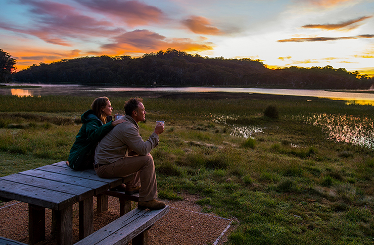 two people rugged up sititng on bench watching the sun set