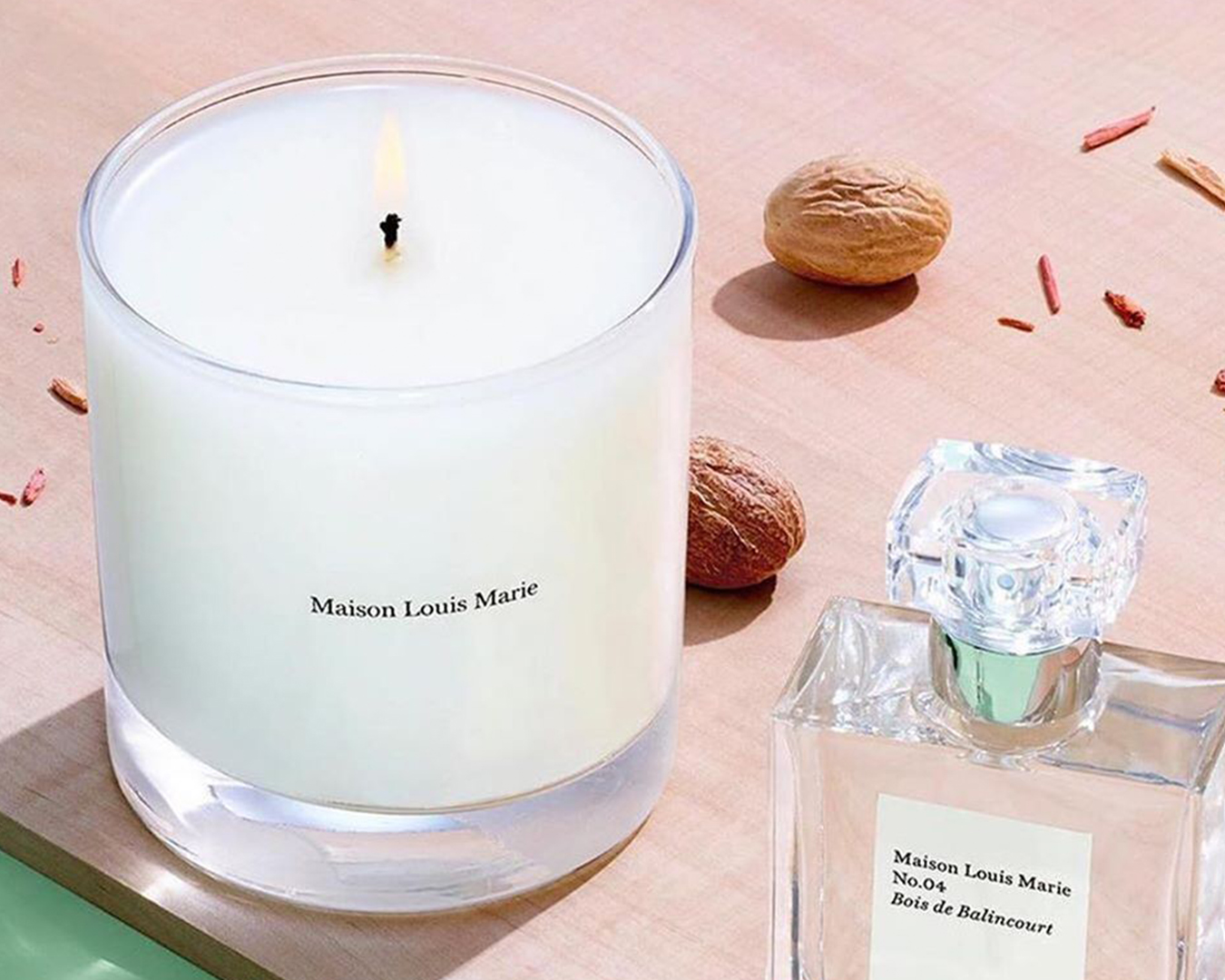 a lit candle sits on a table next to bottle of perfume.