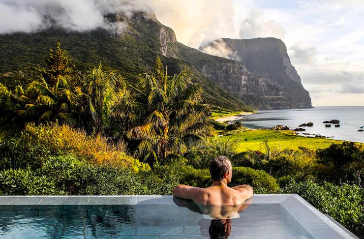 man in pool overlooking mountain