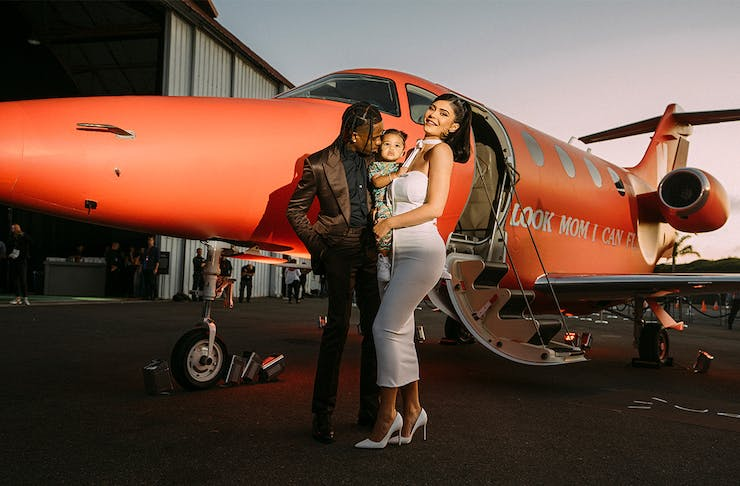 Travis Scott with his wife and child outside a plane.