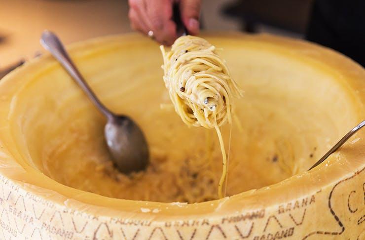 cacio e pepe pasta dipped into giant, creamy cheese wheel