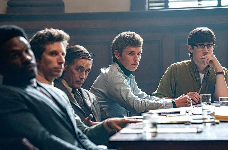 a group of young men sit behind a desk in a courtroom