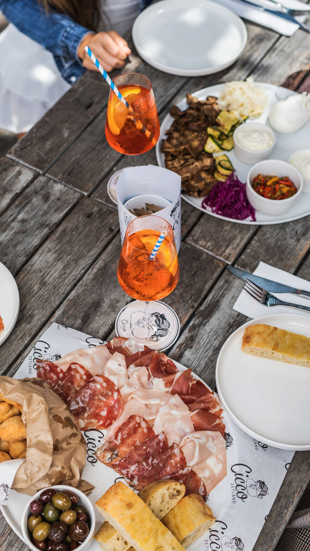 hands reaching out over wooden table loaded with various antipasti boards and spritz