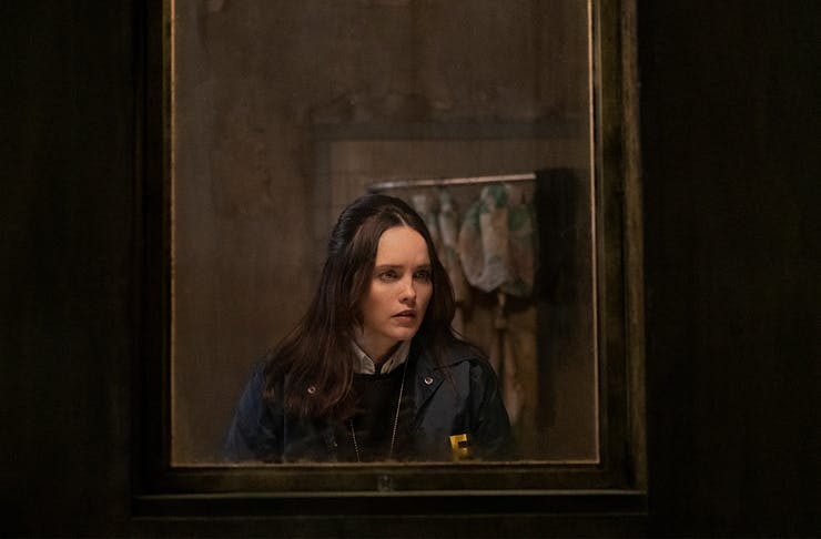 a young woman, peers through a dark window.