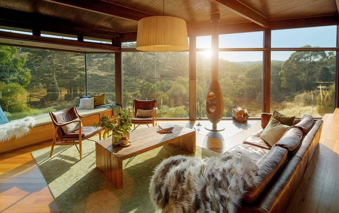 a stunning vista from inside a house with native bushland in the distance and a crackling fireplace.