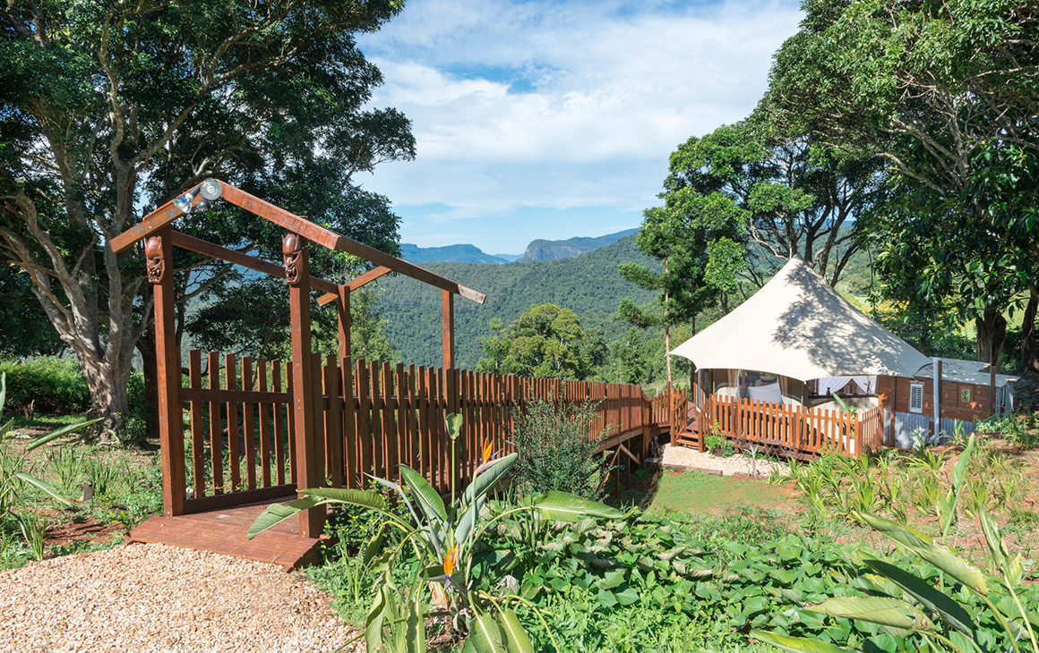 a timber path leads to a white glamping tent called Clouds Safari