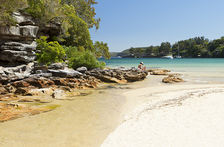 person sitting on rocks of secret beach on sunny day
