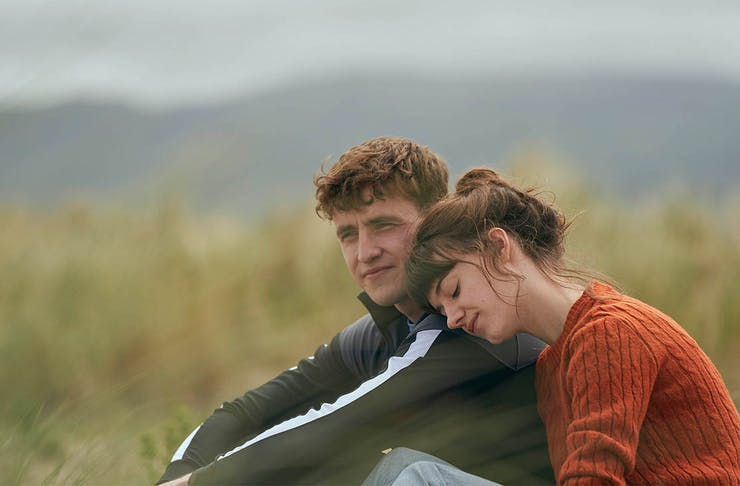 a young man and woman lean on one another in the countryside.