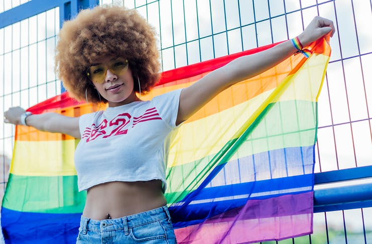 a person wearing a white crop top and jeans proudly holds up a rainbow flag