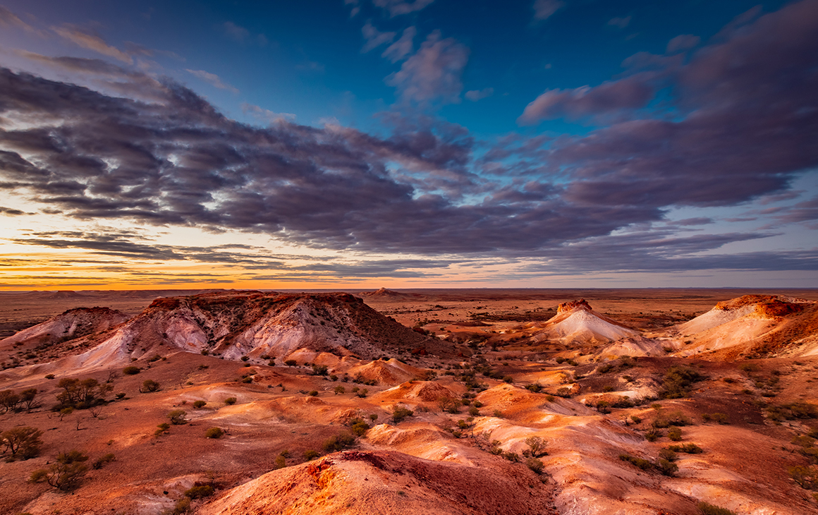 Red rugged rocks cover the surface in outback South Australia. A heavy blue sky with clouds hangs above.