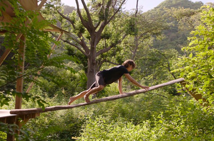 man climbing suspended log in costa rica jungle