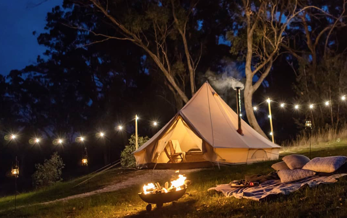 a string of fairy lights hang from a tent at night. In front of it is a crackling fire.
