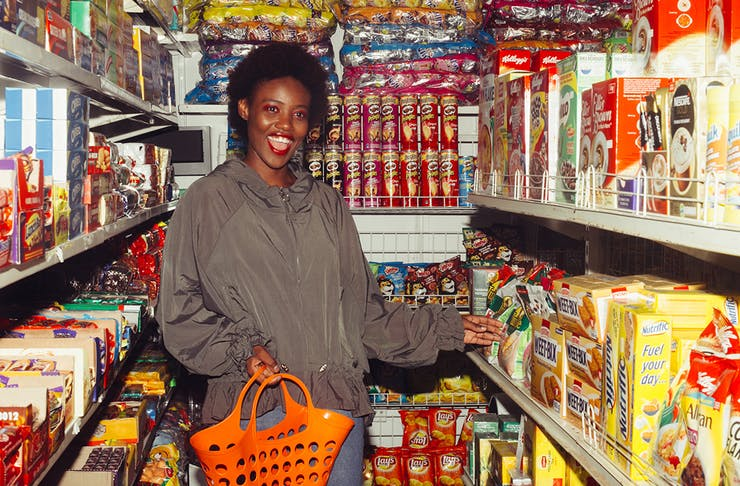 a woman shops in a grocery store, full of colourful aisles.
