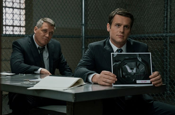 two detectives sit in an interrogation room.