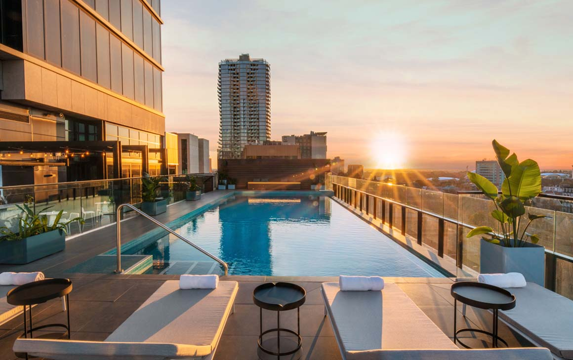 The rooftop pool at sunset of Crowne Plaza