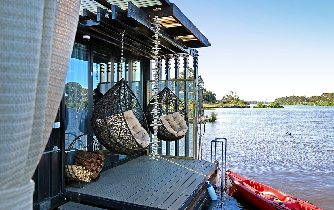 Two hanging chairs on a deck on the river.