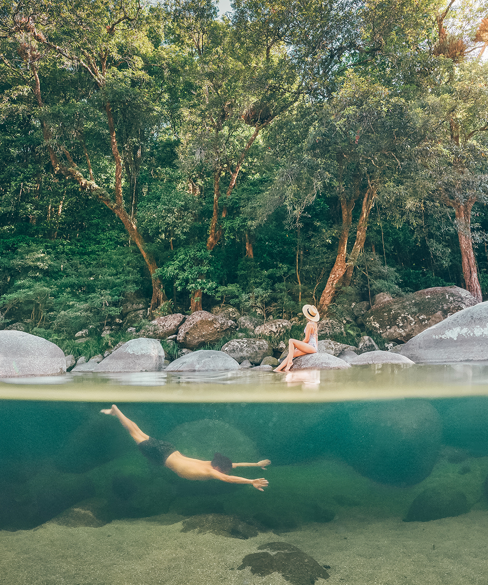 a man swims in the crystal clear water of Mossman Gorge. A woman lounges on a rock.