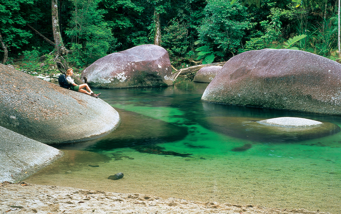 Girl resting on large smooth boulder which is slightly submerged in a crystal clear lake and surrounded by bush land